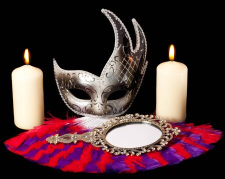 still life photo of disguise mask, mirror, fan and burning candles Stock Photo - 9486772