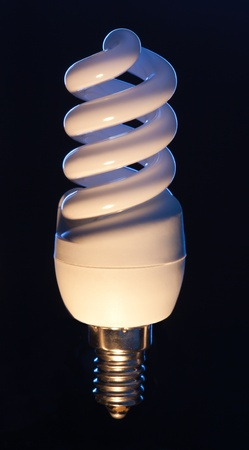 Energy efficient light bulb isolated on black Stock Photo - 9486725