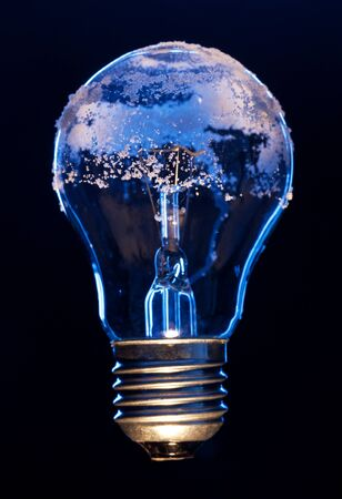 efficiently: Light bulb covered with ice depicting environmental impact concept of electricity efficiently Stock Photo