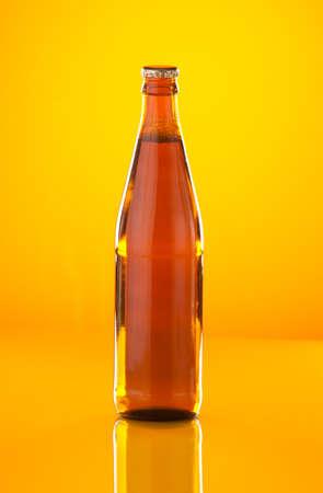 Beer bottle on yellow on yellow background photo