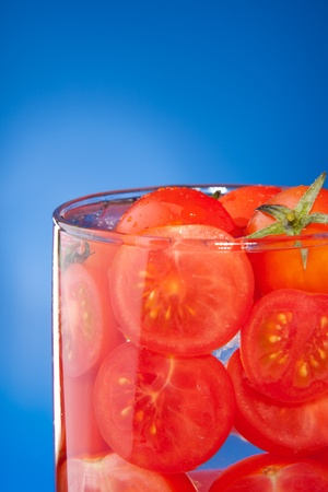 allegory: Close-up of glass with tomato juice allegory made with cherry tomato on blue background Stock Photo