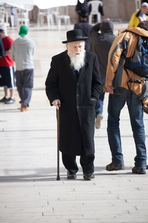 feeble: Jerusalem, Old city, Jewish quarter, Israel, January 05, 2011: Old orthodox Jewish man with walking stick near the Western Wall in Old city Editorial