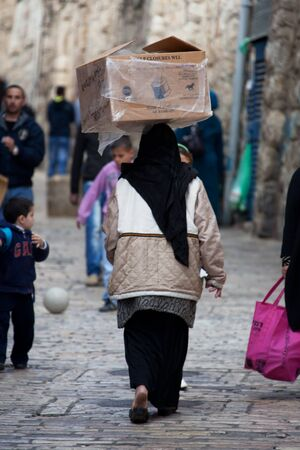 Jerusalem, Old City, Israel, January 05, 2011: Muslim woman walking carry box on her head, El Wad HaGai street