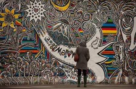 wand graffiti: Berlin, Deutschland, 5. M�rz 2011: Teil der Berliner Mauer auf M�hlenstra�e, The East Side Gallery, untersuchen Touristen graffity