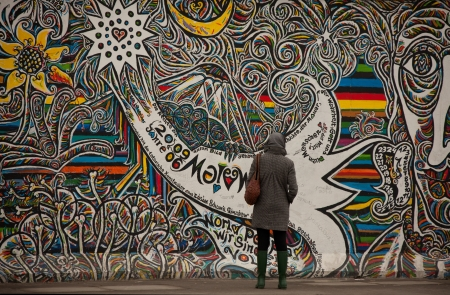 Berlin, Germany, March 05, 2011: Part of Berlin wall on Mühlenstraße , The East Side Gallery, tourists examine graffity