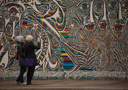 east germany: Berlin, Germany, March 05, 2011: Part of Berlin wall on Mühlenstraße, The East Side Gallery, tourists examine graffity