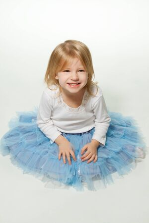 Beautiful little girl sitting on the floor and looking up photo