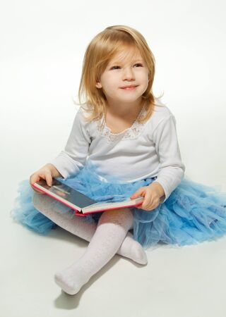 Small girl reading a book and smiling sitting on the floor and looking up photo
