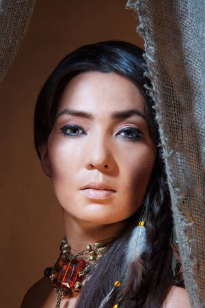 cherokee: American Indian woman looking from the tent - studio photo with professional makeup Stock Photo