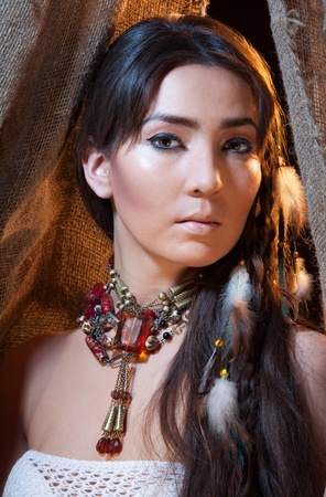 Portrait of American Indian female looking from tent - studio photo with professional makeup