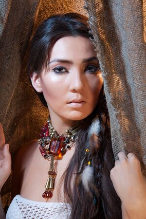 cherokee: Beautiful woman with long hair looking from tent - studio photo with professional makeup