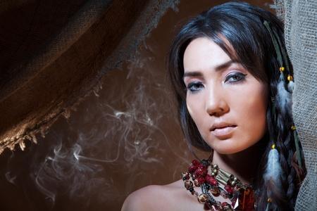 apache: American Indian pitonisa mirando desde una tienda de campa�a con un humo - foto de estudio con maquillaje profesional Foto de archivo