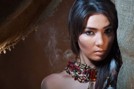 Lovely and passionate look from a tent of American Indian girl - studio photo with professional makeup Stock Photo - 9487146