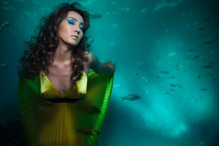Beauty shoot of woman mermaid in yellow dress under the water photo