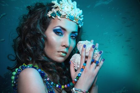 Beauty shoot of a woman holding seashell and pearl necklace and other types of jewelry photo