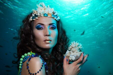 Beauty shoot of a woman underwater with coral in her hands and crown made of photo