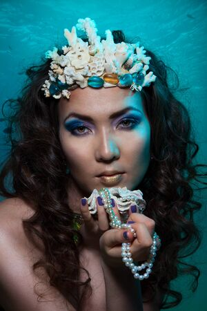 Mermaid with crown of corals holding pearl and seashell photo