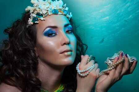 Treasures of underwater world - beauty shoot of a woman with treasures, seashells and coral crown photo