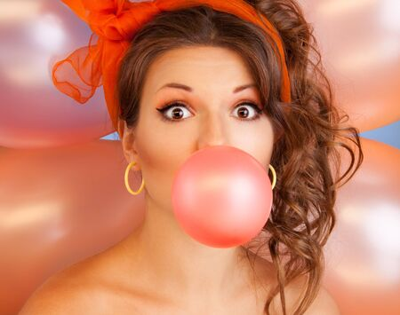 Happy woman at party blowing bubblegum bubble with air baloons on background photo