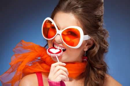 Woman with trendy glasses and red scarf eating lollipop photo