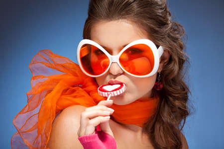 Young beautiful woman with orange scarf lick lollipop and wearing huge sunglasses photo