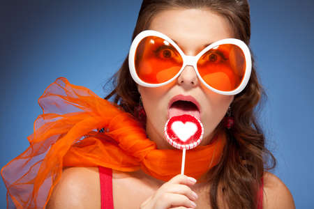 Young funny woman in big orange glasses licking lollipop with her tongue photo