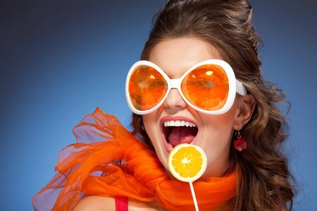 Woman with orange lollipop and laughing with wide opened mouth photo