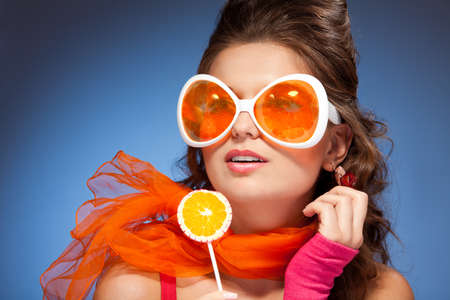 Girl licking lollipop, wearing red scarf with big orange glasses photo