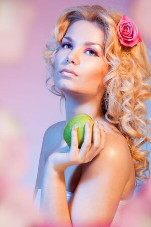 Beauty shoot of Idyllic Eva with green apple, curly blond hair and rose in her hairs photo