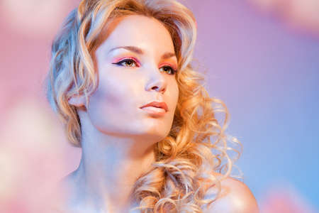 Portrait of a young beautiful woman with curly blond hair with lovely look photo