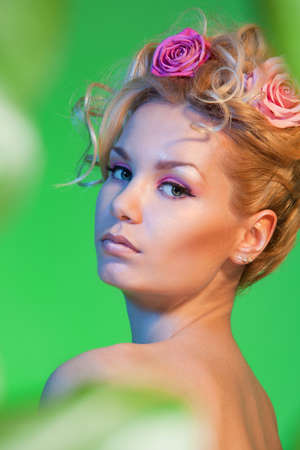 Beauty shoot of blond curly girl with roses in her hair on green background and three quarter turn of a head photo