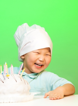 Happy boy with just cooked cake laughing and wearing cooks hat photo