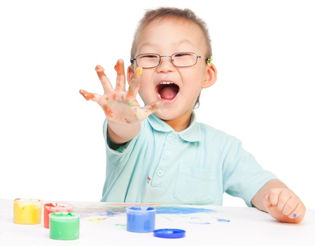 Laughing little painter Chinese boy showing his five with color paint on it Stock Photo - 9486721