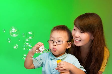 Mother and son blowing soap bubbles with Chinese appearance on green background photo
