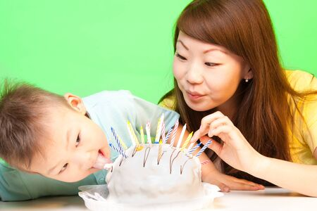 Boy licks his birthday cake with mother nearby and a lot of candles in it photo