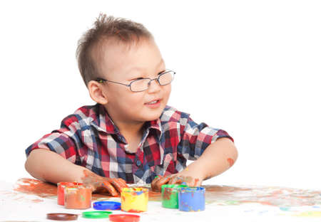 glases: Little Chinese boy drawing with hands paint and warring glases Stock Photo