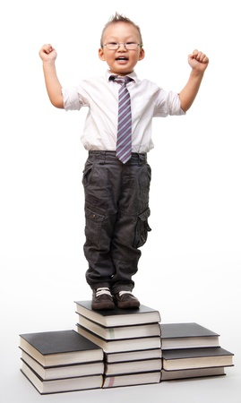 Future successful businessmen - little boy standing on pile of books with his hands up and laughing