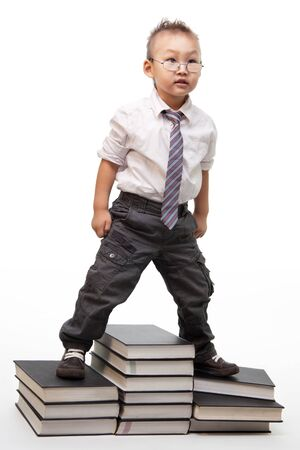 A little Chinese kid with a bossy behavior standing on pile of books photo