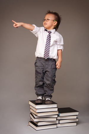 Little Chinese boy entrepreneur standing on stack of books and pointing with his finger