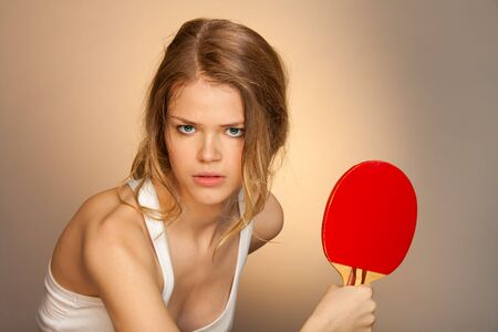 Ready to parry a blow - girl with red ping pong racket in her hand Stock Photo - 9486884
