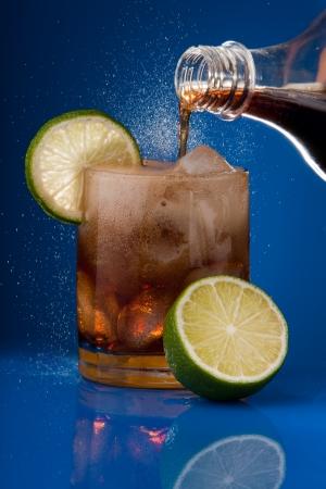 carbonation: Llenado de vidrio con cola aspersi�n de botella con hielo y lim�n Foto de archivo