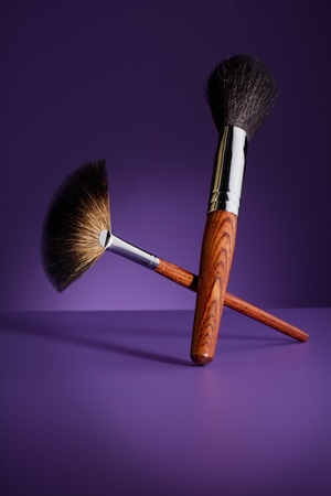 Beautiful effective looking big makeup brushes on purple background photo