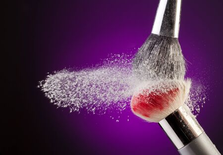 powder blue: Different makeup brushes with powder flying on purple background Stock Photo