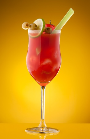 Glass with bloody Mary cocktail with lemon, olives, and celery in glass photo