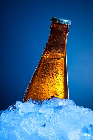 One beer bottle in ice on blue background photo