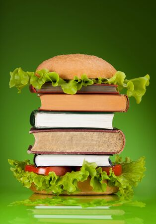 Knowledge fast food concept represented by burger with books on green background