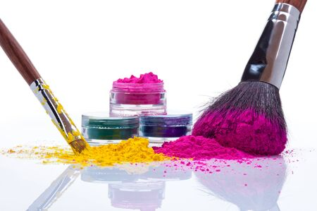 Makeup powder of different colors and brushes