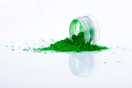 spilled green makeup powder from jar photo