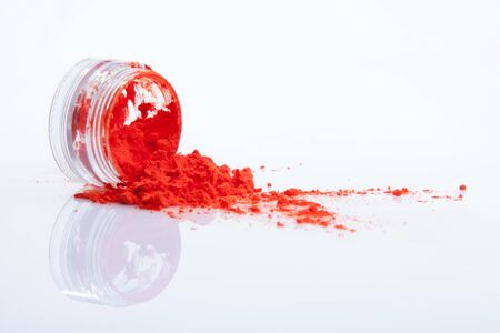 strew: spilled red makeup powder from jar