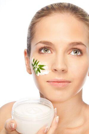 Beautiful women applying moisturizer cosmetic cream on her face depicting concept with green leaves in cream photo